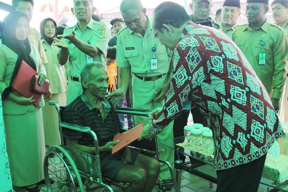 Kepala BKKBN Pusat menyerahkan bingkisan kepada salagh satu warga di Kampung KB Kotamobagu